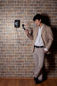 Young asian man with old telephone — Stockfoto