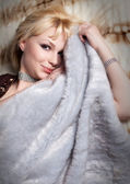 Blond woman dressed in fur lying — Stock Photo