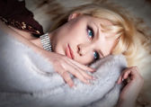 Portrait of sexual blond woman dressed in fur and lingerie lying — Stock Photo