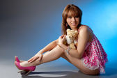 Young girl in pink dress with a toy bear — Стоковое фото