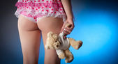 Young woman in lingerie holding a teddy bear — Stock Photo