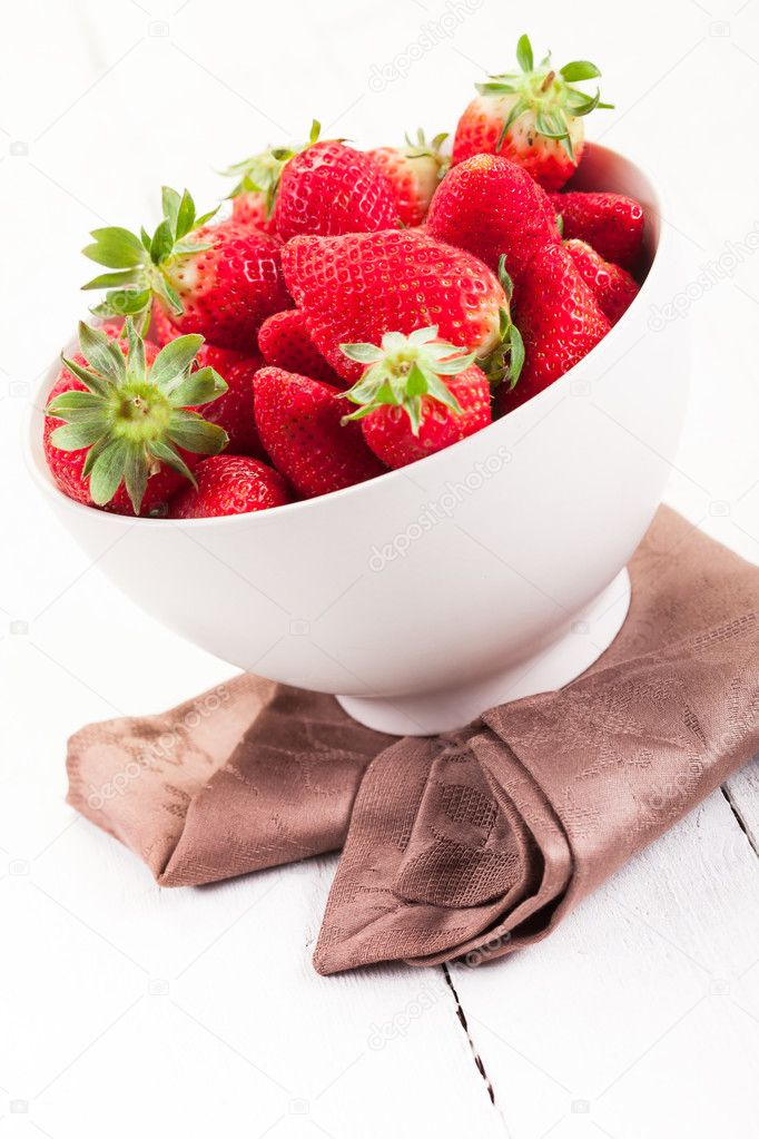 Delicious strawberries inside a bowl on white wooden table — Stock Photo #10105782