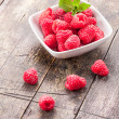Raspberries on wooden table — Stock Photo