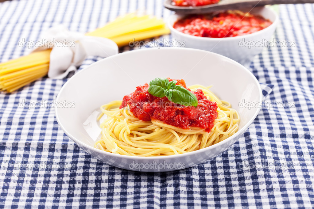 Italian Spaghetti with tomato sauce on traditional home towel — Stock Photo #10545544
