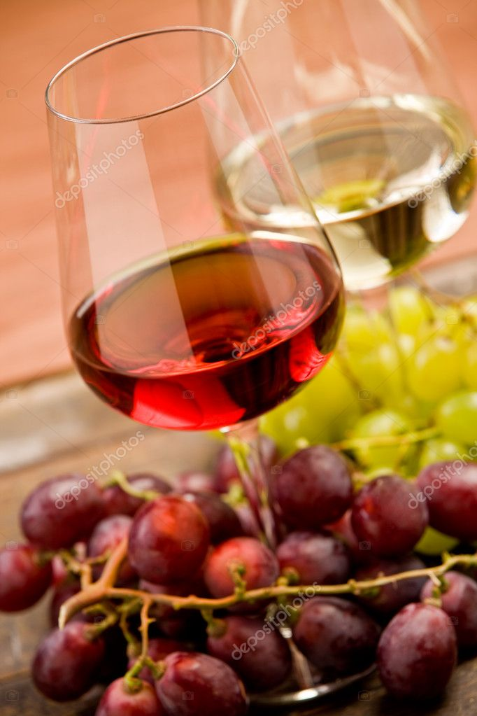 Rose and white wine on wooden table with red and white grapes around  Stock Photo #8509764