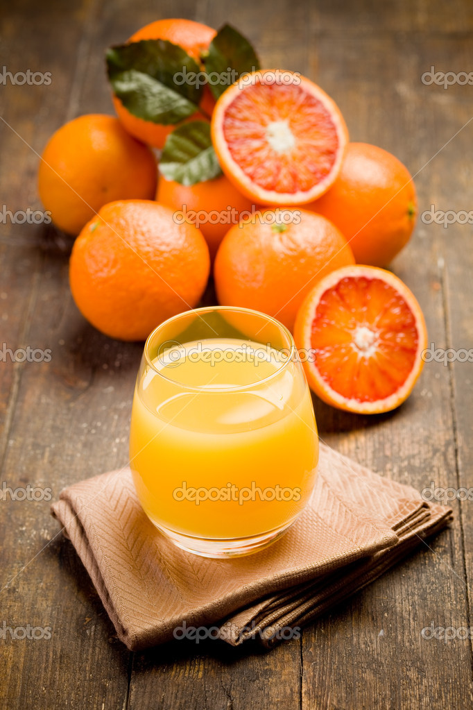 Fresh squeezed orange juice on ancient wooden table — Stock Photo #8612594