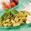 Pasta with pesto on green glass table - Stock Photo