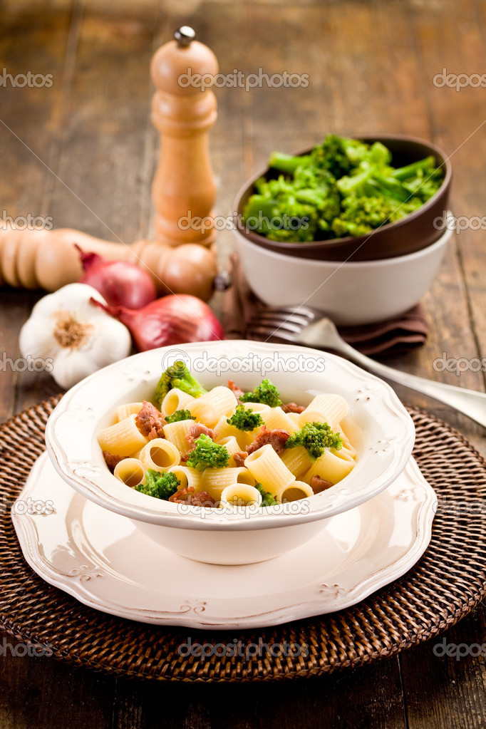 Photo of delicious pasta with sausage and broccoli on wooden table — Stock Photo #9135426
