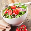 Arugula Salad with tomatoes and onion rings - Stock Photo