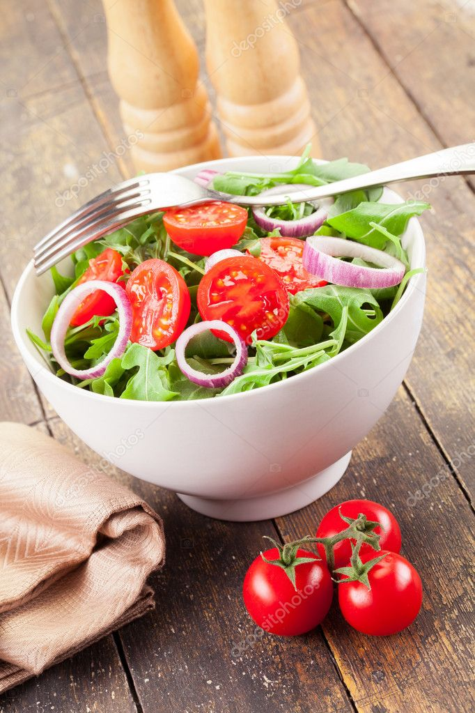 Delicious light arugula salad with tomatoes and onion rings on wooden table — Stock Photo #9930587