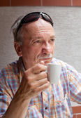 Old man drinking cup of coffee — Stock Photo