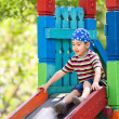 Boy  playing on slide — Stockfoto