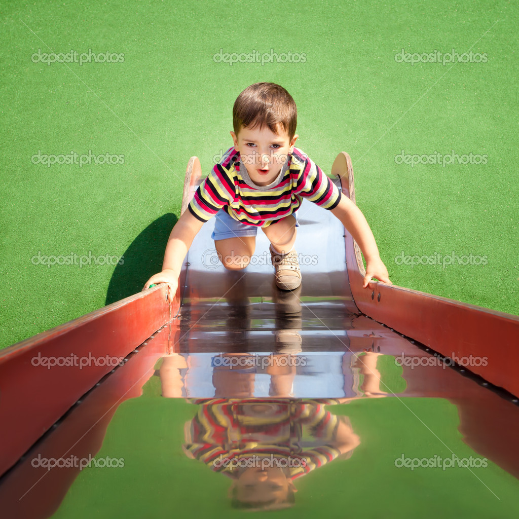 Cute young boy climbing up a slide on playground — Stock Photo #10514049