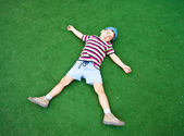 Boy laying on plastic green grass — Stock fotografie