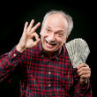 Elderly man showing fan of money — Stockfoto