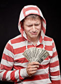 Crying young man with money — Stock Photo
