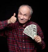 Elderly man showing fan of money — ストック写真