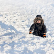 Stock Photo: Young boy sitting on snow