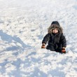 Young boy sitting on the snow — 图库照片