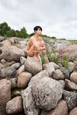 Nude woman sitting on stones — Stock Photo