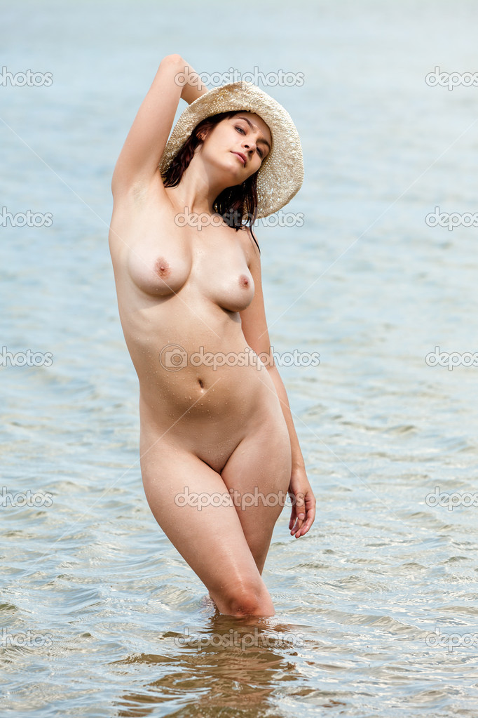 Beautiful naked wet woman in a white hat standing in the sea and sunbathing — Stock Photo #9672304