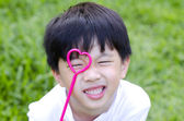 Cute Asian boy holding a heart shape on his eye — Stock Photo