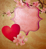 Pink heart hanging on the blooming tree brunch on grunge dark bl — Stock Photo