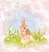 Brown hare or rabbit sitting in the grass with easter eggs and d — Stock Photo