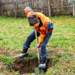 Boy digging in the ground - Stock Photo