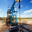 Oil pump under blue sky - Stock Photo