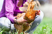 Woman catching a chicken outdoor — Stock Photo