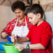 Grandson and grandmother making cookies - Stock Photo