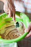 Senior woman's hands stirring cocoa cream with spatula — Stock Photo