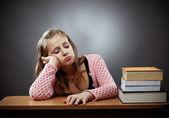 Ongelukkig schoolmeisje met een stapel boeken — Stockfoto