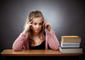 Unhappy schoolgirl with a stack of books — Stock Photo