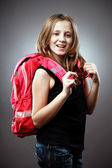Blond schoolgirl with backpack in studio — Stock Photo