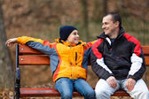 Father and son on a bench in park — Stock Photo