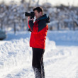 Tourist with camera in the winter — Stock Photo