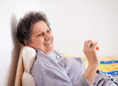 Old woman sitting on bed — Stock Photo