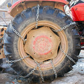 Huge tractor tyre with chains — Stock Photo