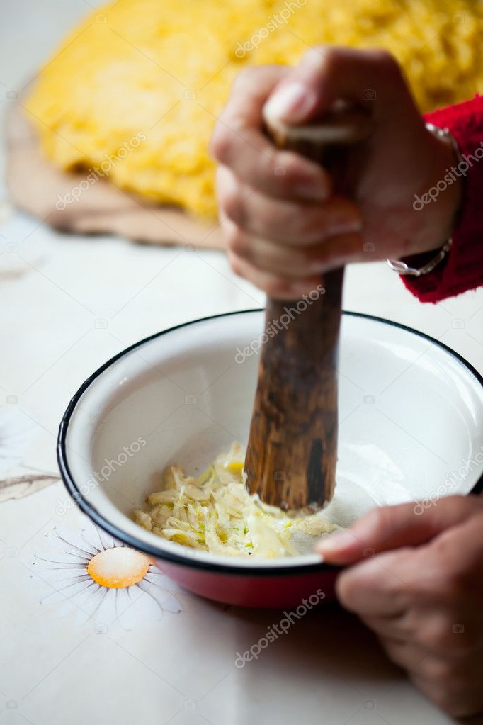Woman hands crushing raw garlic in a bowl — Stock Photo #9623564
