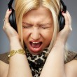 Young lady shouting or singing on the song in the headphones - Stock Photo