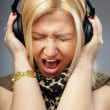 Young lady shouting or singing on the song in the headphones — Stock Photo