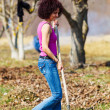 Young woman with a rake in an orchard — Stock Photo #9823340