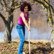 Young woman with a rake in an orchard — Stockfoto