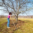 Young woman with a rake in an orchard — ストック写真