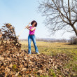 Young womwith rake in orchard — Stockfoto #9823710