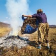 Stock Photo: Senior rural woman burning fallen leaves