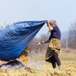 Senior rural woman burning fallen leaves — Stockfoto