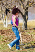 Young woman with a rake in an orchard — Stock Photo
